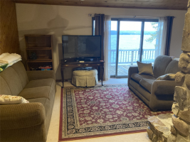 Open living room with sliding glass door leading to upper deck. Amazing lake view for outdoor dining!