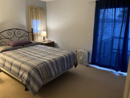 Master bedroom on lake side with sliding glass door to upper deck